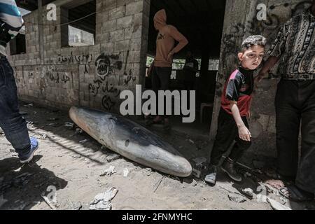 Gaza-Stadt, Palästinensische Gebiete. Mai 2021. Palästinenser inspizieren eine nicht explodierte Bombe, die von einem israelischen F-16-Kampfflugzeug in der Nachbarschaft von Rimal abgeworfen wurde, inmitten des eskalierenden Ausflackers der israelisch-palästinensischen Gewalt. Kredit: Mohammed Talatene/dpa/Alamy Live Nachrichten