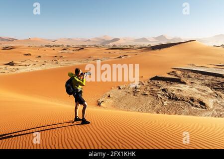 Fotograf, der in Deadvlei, Namib-Naukluft Nationalpark, Namibia, Afrika fotografiert. Getrockneter Boden mit Sand in der Namib Wüste bei Sonnenuntergang. Landschaftsfotografie