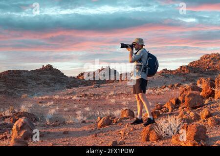 Fotograf, der in Felsen der Namib-Wüste, Namibia, Afrika fotografiert. Rote Berge und Sonnenuntergang Himmel im Hintergrund. Landschaftsfotografie