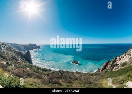 Luftaufnahme Panorama Meerblick, Draufsicht, erstaunliche Natur Hintergrund. Wilder, abgelegener Strand mit felsigen Bergen und azurblauem Wasser an sonnigen Tagen. Nie endend