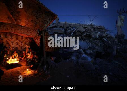 Palästinenser aus der Familie Zawaraa sitzen in einem provisorischen Zelt in der Nähe von Kerzen inmitten der Trümmer ihrer Häuser, die durch israelische Luftangriffe während der israelisch-palästinensischen Kämpfe im Gazastreifen am 25. Mai 2021 zerstört wurden. Bild aufgenommen am 25. Mai 2021. REUTERS/Mohammed Salem