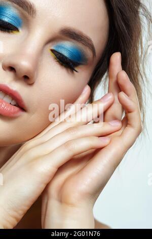Nahaufnahme einer jungen Frau mit Händen in der Nähe des Gesichts und halb geschlossenen Augen. Weiblich mit Abend vogue Auge Schönheit Make-up. Gesicht mit perfekter Haut, brüllen