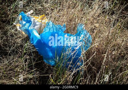 Rustavi, Georgien. 3. Juni 2021. Blaue Plastiktüte auf dem Boden. Beweise für Naturverschmutzung.