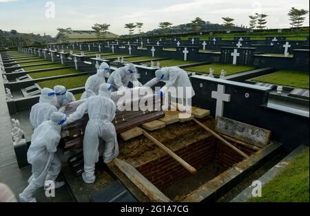 Klang, Selangor, Malaysia. Juni 2021. Mitarbeiter des Bestattungsdienstes, die persönliche Schutzausrüstung (PSA) tragen, bereiten sich darauf vor, den Sarg eines Opfers der Coronavirus-Krankheit (COVID-19) auf dem Friedhof zu begraben.Quelle: Kepy/ZUMA Wire/Alamy Live News