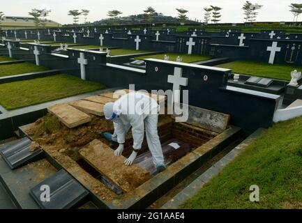 Klang, Selangor, Malaysia. Juni 2021. Bestattungsmitarbeiter mit persönlicher Schutzausrüstung (PSA) begraben den Sarg eines Opfers der Coronavirus-Krankheit (COVID-19) auf dem Friedhof.Quelle: Kepy/ZUMA Wire/Alamy Live News