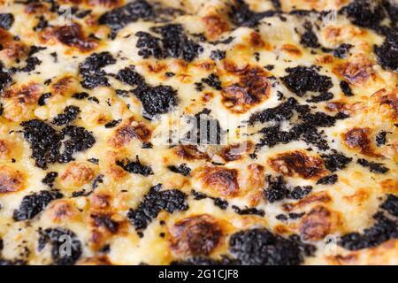 Nahaufnahme der Pizza mit Trüffeln und Käse. Makroaufnahme köstlicher Produkte.