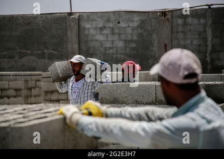 Gaza, Palästina. Juni 2021. Palästinenser arbeiten in einer Fabrik, die die Trümmer der Gebäude wiederverwertet, die während des Konflikts zwischen der Hamas und Israel im Mai 2021 zerstört wurden.der Prozess der Wiederverwertung der Trümmer der zerstörten Gebäude vor fast drei Wochen in Gaza, um Steine zu blockieren, die für zukünftige Rekonstruktionen nützlich sind, läuft. (Foto von Ahmed Zakot/SOPA Images/Sipa USA) Quelle: SIPA US/Alamy Live News