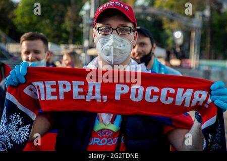 """Moskau, Russland. 12. Juni 2021 EIN Fußballfan mit Atemschutzmaske und Handschuhen besucht die Fanzone, in der das UEFA Euro 2020-Spiel der Gruppe B zwischen Belgien und Russland in der Nähe des Luschniki-Stadions in Moskau, Russland, übertragen wird. Auf dem Fanschal steht die Inschrift """"vorwärts, Russland"""""""
