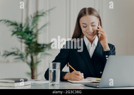 Positive junge Geschäftsfrau, die telefoniert und Notizen schreibt