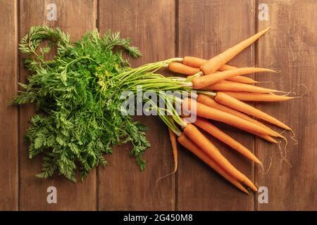 Frische Bio-Roh-Baby-Karotten auf einem dunklen rustikalen Holzhintergrund