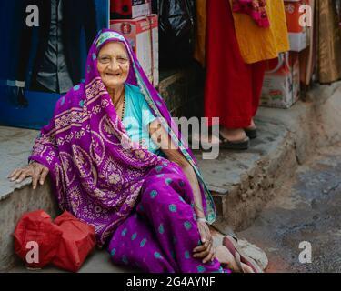 Ältere Frau in farbenfrohen traditionellen indischen Kleidern, die sich vom Spaziergang entlang der Straße in Delhi, Indien, ausruhen.