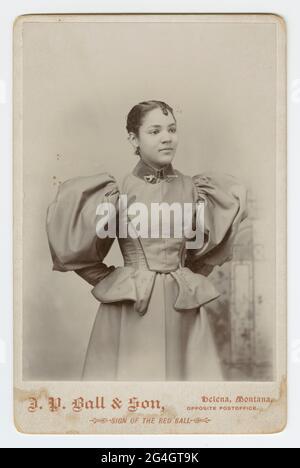 Eine Schwarz-Weiß-Fotografie einer nicht identifizierten afroamerikanischen Frau, fotografiert im J. P. Ball & Son Studio in Helena, Montana. Das Foto ist auf einer hellen Pappe angebracht, auf der der Name und die Position des Fotostudios auf der Vorderseite entlang der Unterseite aufgedruckt sind. Die Frau steht und trägt ein helles Kleid mit Hammelärmeln und einer Schößchen-Taille. Das Kleid hat einen hohen, dunklen Samtkragen und sie trägt einen schwertförmigen Pin durch die Vorderseite in der Mitte. Ihre Arme sind hinter ihrem Rücken versteckt und sie sieht leicht nach links. Die Rückseite ist leer.