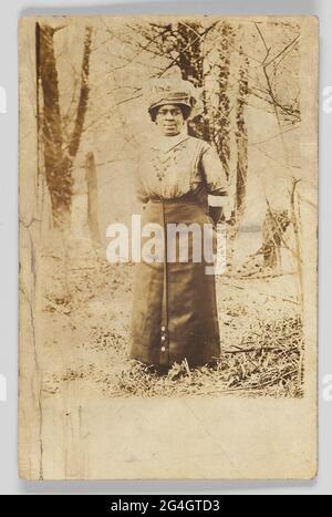 Eine Fotopostkarte einer nicht identifizierten Frau, die in einem Waldgebiet steht. Sie ist im Stehen, gegenüber der Kamera und blickt rechts vom Foto. Sie trägt einen langen Rock und ein Hemd mit einem großen Hut an. Die Rückseite der Fotopostkarte ist nicht verwendet und hat einen schwarzen Druck auf [POSTKARTE] und Leerzeichen für [KORRESPONDENZ] und [NAME UND ADRESSE]. In der oberen rechten Ecke befindet sich ein [CYKO]-Stempel. Auf der Rückseite sind auch Informationen über den Hersteller der Postkarte gedruckt.