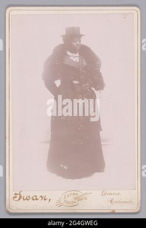 Diese Schwarz-Weiß-Fotografie, die Justus C. Swan zugeschrieben wird, zeigt ein Porträt einer nicht identifizierten afroamerikanischen Frau, die sich eine Vierteldrehung weiter links von ihr befindet. Sie blickt in diese Richtung, ihr Kopf ist fast im Profil gedreht. Sie trägt einen dunklen, bodenlangen Rock und eine knielange Jacke mit Beinärmeln. Eine helle Schärpe ist um ihre Taille und sie hat einen gekräuselten, hellen Kragen. Ihre rechte Hand befindet sich in ihrer Jackentasche und sie hält ein kleines, glänzendes Objekt in ihrer linken Hand, die mit einem Handschuhen beherzt ist. Eine Pelzstola ist um ihren Hals und ihre Schultern drapiert, und sie trägt eine kurze