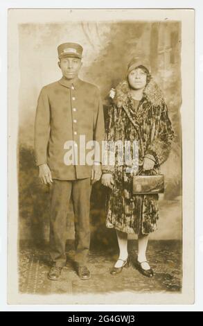 """Schwarz-weiße Fotopostkarte, die nie gestempelt und verschickt wurde, aber auf der Rückseite den Namen """"Omer Ester"""" mit Bleistift geschrieben hat. Das Bild auf der Postkarte zeigt Pullman Porter, Omer Ester, in seiner vollen Portier-Uniform, einschließlich Pullman Porter Cap. Neben ihm steht eine nicht identifizierte afroamerikanische Frau, die einen Samtmantel in voller Länge mit Pelzbesatz am Kragen und an den Ärmeln trägt. Sie trägt einen Frauenhut im Stil der 1920er Jahre und hält eine Handtasche in ihrer rechten Hand. Sie befinden sich in einem Fotostudio, das vor einer gemalten Kulisse mit einem Karpfen im orientalischen Stil steht"""