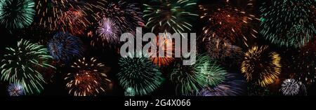Buntes Feuerwerk in schwarzem Nachthimmel, breites Banner für den Hintergrund des Urlaubs