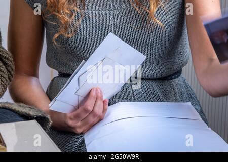 Eine junge Frau, die einige Fotos auf der Hand hält und einige andere überprüft