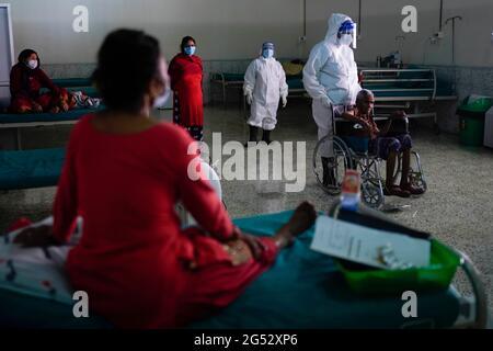 Kathmandu, Nepal. Juni 2021. Gesundheitshelfer vor Ort eskortieren die 92 Jahre alte Kalika Devi Bastola nach der Genesung von COVID-19 im Radiha Soami COVID Isolation & Oxygen Therapy Center in Kathmandu, Nepal, am Freitag, den 25. Juni 2021. Kredit: Skanda Gautam/ZUMA Wire/Alamy Live Nachrichten