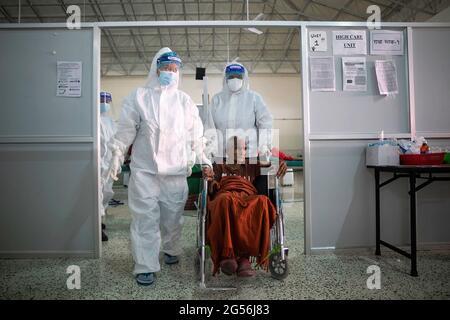 Kathmandu, Nepal. Juni 2021. Gesundheitshelfer vor Ort, die persönliche Schutzausrüstung (PSA) tragen, begleiten die 94 Jahre alte Kalika Devi Bastola im Rollstuhl, als sie nach ihrer Genesung aus dem Isolationszentrum in Kathmandu zu ihrem Haus aufbricht. Kredit: SOPA Images Limited/Alamy Live Nachrichten