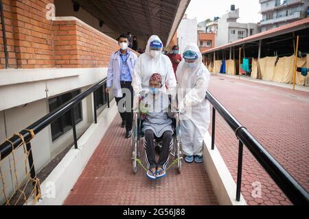 Kathmandu, Nepal. Juni 2021. Gesundheitshelfer vor Ort, die persönliche Schutzanzüge (PSA) tragen, begleiten einen sehbehinderten 74-jährigen Kaile Tamang im Rollstuhl, als er nach seiner Genesung vom Isolationszentrum in Kathmandu in sein Haus aufbricht. Kredit: SOPA Images Limited/Alamy Live Nachrichten