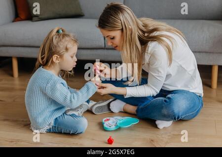 Mutter und kleine Tochter malen ihre Nägel mit Spielzeug-Nagellack. Kind spielt mit Mutter zu Hause. Konzept der guten Elternschaft und glückliche Kindheit, Familie
