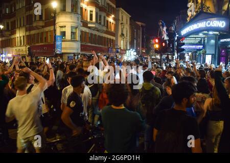 London, Großbritannien. Juli 2021. Fußballfans feiern auf dem Leicester Square nach dem Sieg Englands über Dänemark beim Halbfinale der Euro 2020. Tausende von jubelenden Anhängern versammelten sich im Zentrum von London, um Englands Platz beim Finale der Fußballmeisterschaft im Wembley Stadium zu feiern.