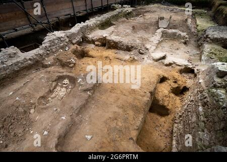 Ein Blick auf die Überreste eines Mönchs aus dem 12. Jahrhundert auf dem North Green in Westminster Abbey, London, während einer Vorschau, bevor die archäologische Ausgrabungsstätte im Rahmen der Hidden Highlights Tour für die Öffentlichkeit zugänglich wird. Das Skelett, teilweise mit Erde bedeckt, wurde während der Ausgrabungen der Großen Sakristei ausgegraben, wo die Mönche Gewänder, Altarwäsche und andere heilige Gegenstände, die in der Messe verwendet wurden, aufbewahrten. Bilddatum: Mittwoch, 7. Juli 2021.