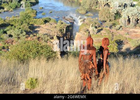 NAMIBIA. JUNGE HIMBAS-FRAUEN, DIE IN DER NÄHE DER EPUPA-WASSERFÄLLE DES KUNENE-FLUSSES, DER NATÜRLICHEN GRENZE ZU ANGOLA, NACH WASSER SUCHEN. FAST 8 000 HIMBAS LEBEN