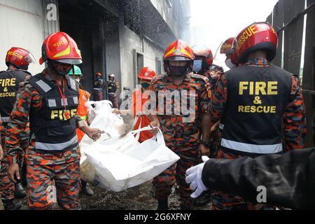 Narayanganj. Juli 2021. Feuerwehrleute tragen den Leichnam eines Opfers nach einem Brand in der Saftfabrik in Narayanganj, Bangladesch, 9. Juli 2021. Mindestens 51 Arbeiter starben als eine Saftfabrik im Distrikt Narayanganj in Bangladesch, etwa 20 km von der Hauptstadt Dhaka entfernt, und brannte am Donnerstag, sagte ein hochrangiger Beamter am Freitag. Quelle: Xinhua/Alamy Live News