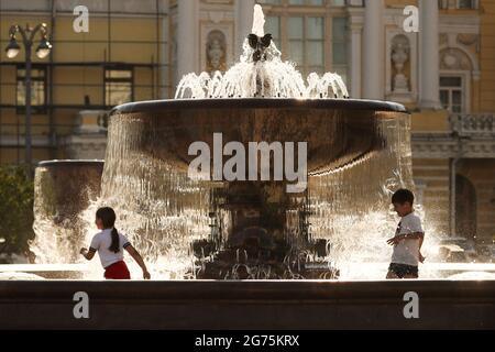 Moskau, Russland. Juli 2021. Kinder kühlen sich in einem Brunnen vor dem Bolschoi-Theater ab. Quelle: Mikhail Tereschtschenko/TASS/Alamy Live News