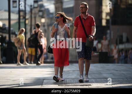 Moskau, Russland. Juli 2021. Eine Frau und ein Mann gehen eine Straße entlang. Quelle: Mikhail Tereschtschenko/TASS/Alamy Live News