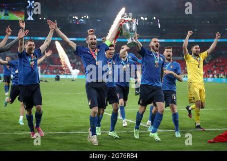Die Italiener Giorgio Chiellini und Leonardo Bonucci tragen die Trophäe und feiern mit Teamkollegen, nachdem sie nach dem UEFA-EM-Finale 2020 im Wembley Stadium, London, den Elfmeterschießen gewonnen haben. Bilddatum: Sonntag, 11. Juli 2021.