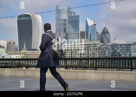 London, Großbritannien. Juli 2021. Ein Mann geht am London Bridge Thames Path vorbei an einem Blick auf die Skyline von London. Kredit: SOPA Images Limited/Alamy Live Nachrichten