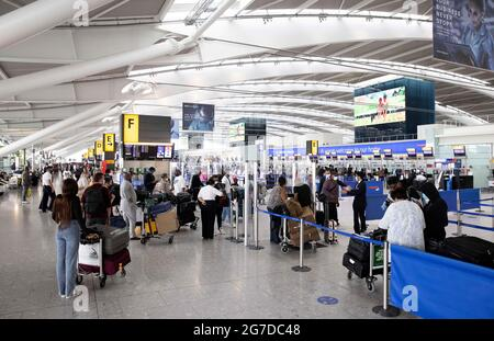 London, Großbritannien. Juli 2021. Passagiere im Terminal 5. Passagiere in Heathrow, die sich dem 19. Juli nähern, und die Reisebeschränkungen für bestimmte Länder werden aufgehoben. Gestern (12. Juli) gab es lange Schlangen in Heathrow, als sich viele Sicherheitsbeamte selbst isolieren mussten. Die Immigration Service Union hat gewarnt, dass Reisende bis zu 6 Stunden Verspätung haben können, wenn die Einschränkungen gelockert werden. Kredit: Mark Thomas/Alamy Live Nachrichten