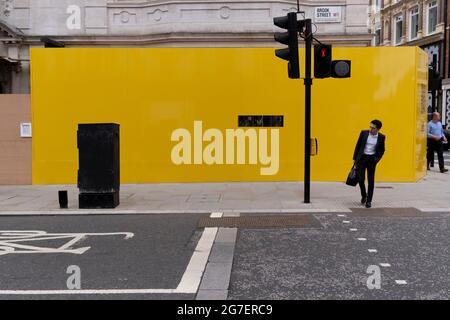Ein Geschäftsmann hält inne, um den entgegenkommenden Verkehr zu kontrollieren, bevor er am 12. Juli 2021 in London, England, die Brook Street in Mayfair überquert.