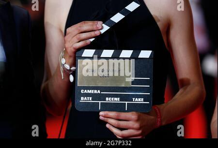 Die 74. Filmfestspiele von Cannes - Vorführung des Films 'Haut et fort' (Cascardo Beats) im Wettbewerb - Ankunft des Roten Teppichs - Cannes, Frankreich 15. Juli 2021. Ein Gast hält ein Filmklappertafel. REUTERS/Johanna Geron