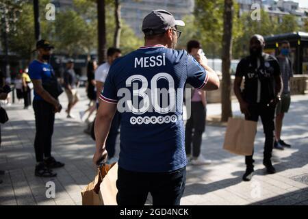 Paris, Frankreich. August 2021. Ein Unterstützer trägt ein Trikot des argentinischen PSG-Fußballspielers Lionel Messi, das er am 11. August 2021 im Laden des Fußballclubs Paris-Saint-Germain (PSG) auf der Champs Elysees in Paris gekauft hat. Messi unterzeichnete am 10. August 2021 einen zweijährigen Vertrag mit PSG mit der Option eines zusätzlichen Jahres. Der 34-Jährige wird in Paris die Nummer 30 tragen, die er zu Beginn seiner beruflichen Laufbahn bei Barca hatte. Foto von Raphael Lafargue/ABACAPRESS.COM Quelle: Abaca Press/Alamy Live News
