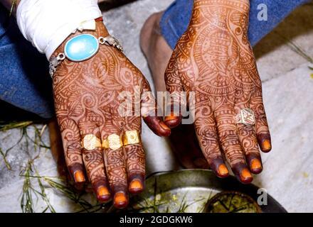 Das wunderschöne Kunstwerk von Henna Mehndi auf den schönen Händen des indischen Bräutigams wird Henna-Farbstoff während des indischen Hochzeitsfestes auf die Hand des Mannes aufgetragen