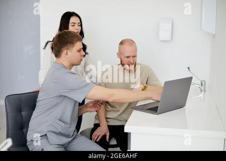 Ein junger Zahnarzt berät zwei Patienten.