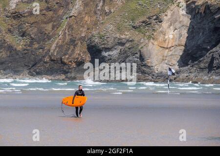 Eine alleinreisende Frau mit einem angeheuerten orangefarbenen Surfbrett, die am Mawgan Porth Beach in Cornwall aus dem Meer läuft; Staycation Cornish