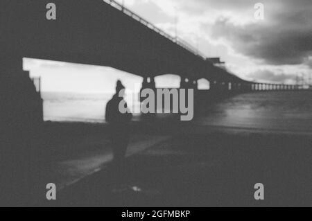Ein dunkles Konzept für psychische Gesundheit . Einer geheimnisvollen Frau, die unter einer modernen Brücke mit einem verschwommenen, abstrakten Schnitt zurück in die Kamera kommt.