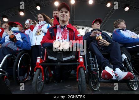 MOSKAU, RUSSLAND – 9. SEPTEMBER 2021: Der Paralympische Schwimm-Bronzemedaillengewinnerin Vladimir Danilenko (C Front) nimmt an einer Zeremonie Teil, um die russischen Athleten zu ehren, die als Team RPC bei den Paralympischen Sommerspielen 2020 auf dem Roten Platz teilgenommen haben. Die Sommer-Paralympischen Spiele in Tokio liefen vom 24. August bis zum 5. September. Russische Athleten gewannen 36 Goldmedaillen, 33 Silbermedaillen und 49 Bronzemedaillen und belegten damit den vierten Platz in der Paralympischen Medaillenzählung. Sergei Karpuchin/TASS