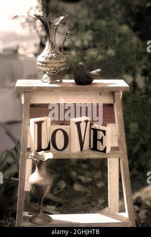 Die Worte der Liebe gesammelt mit Vintage Vasen und einem Vogel auf einer Leiter im Garten