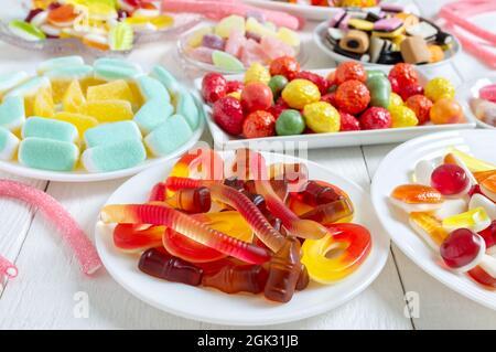 Verschiedene leckere bunte Gummy Bonbons auf Tellern. Vertikale Ansicht