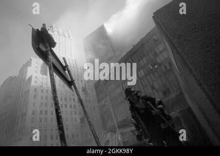FDNY-Feuerwehrmann, der aus dem Rauch von New York City auftaucht, während die Twin Towers während des Angriffs von islamischen Terroristen am 11. September 2021 brennen. (USA)