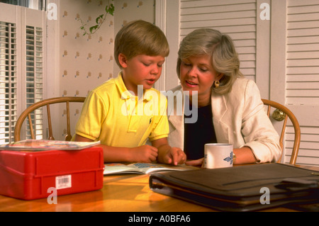 Mutter und Sohn lesen Buch, bevor Mutter klingelt, veröffentlichte CF22586 zu arbeiten - Stockfoto