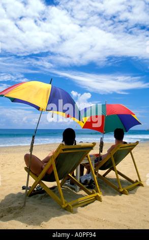 Paar, sitzen unter bunten Sonnenschirmen Hikkaduwa Strand - Stockfoto