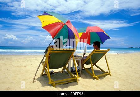 Paar, sitzen unter bunten Sonnenschirmen Hikkaduwa Strand Sri lanka - Stockfoto