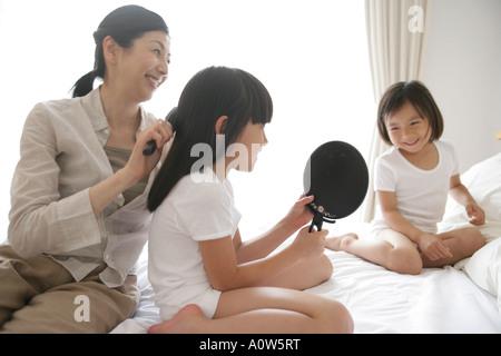 Seitenansicht eines Mädchens und ihre Schwester auf dem Bett sitzt mit ihrer Mutter, die ihr Haar Bürsten - Stockfoto