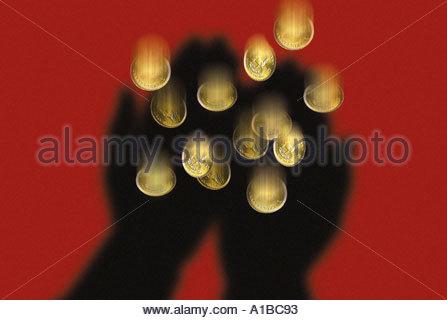 Schatten der Hände fangen Goldmünzen - Stockfoto